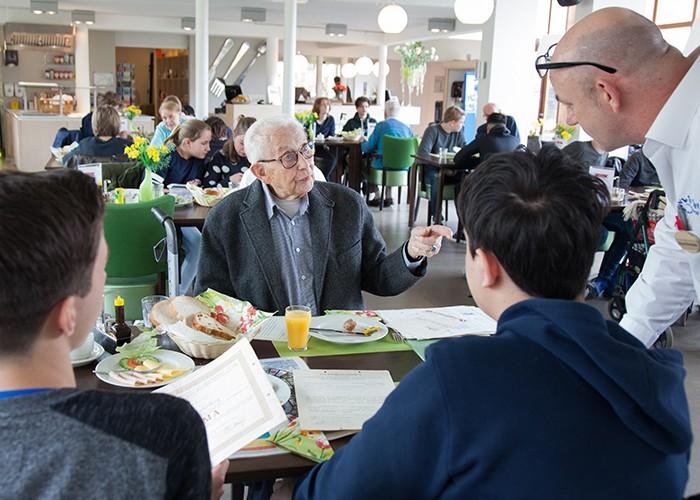 oudere man legt uit aan jongeren over zijn beroep
