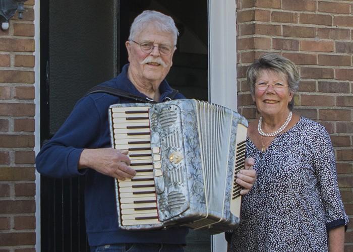 Man met harmonica bij de voordeur